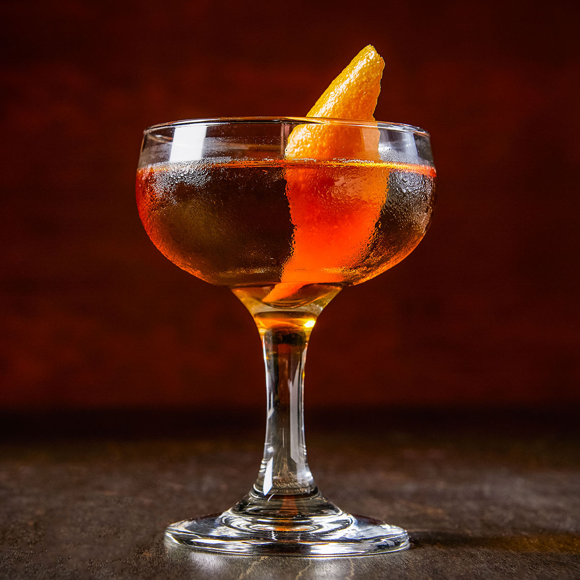 Orange cocktail in a coupe glass with orange peel garnish